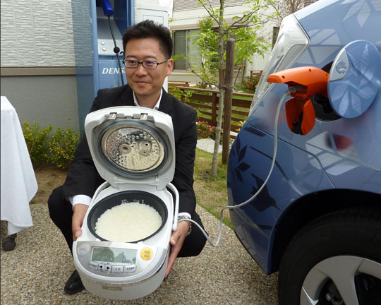 Drive-in rice: A Toyota Motor Corp. worker demonstrates a rice cooker that works off power from the battery of a Toyota plug-in hybrid vehicle in Toyota, Aichi Prefecture, on Monday. | KYODO