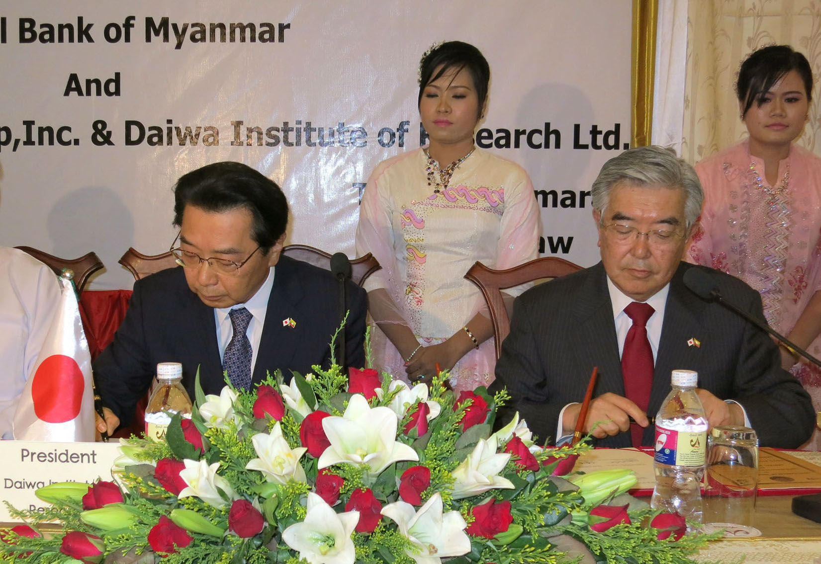 Getting their foot in the door: Tokyo Stock Exchange President Atsushi Saito (right) and Daiwa Institute of Research President Takashi Fukai sign an agreement to help Myanmar set up its first stock exchange, in Naypyitaw on May 29. | KYODO