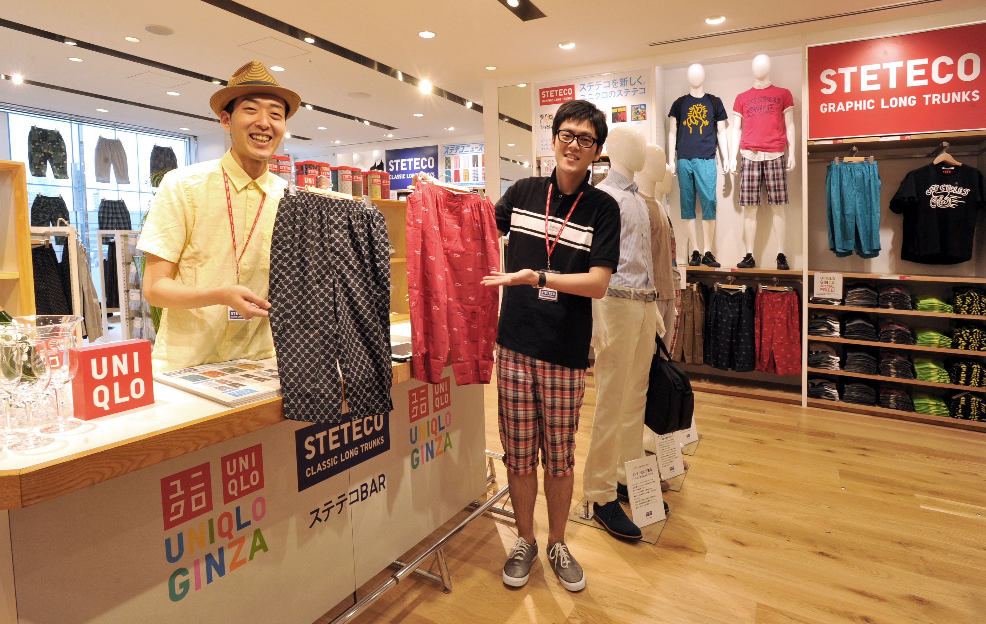 Breaking with convention: Uniqlo 'steteco bartenders' Sokichi Hotta (left) and Itaru Nakamaniwa show and wear brightly colored 'suteteko' underwear at the company's flagship store in Ginza, Tokyo, on Monday. | YOSHIAKI MIURA