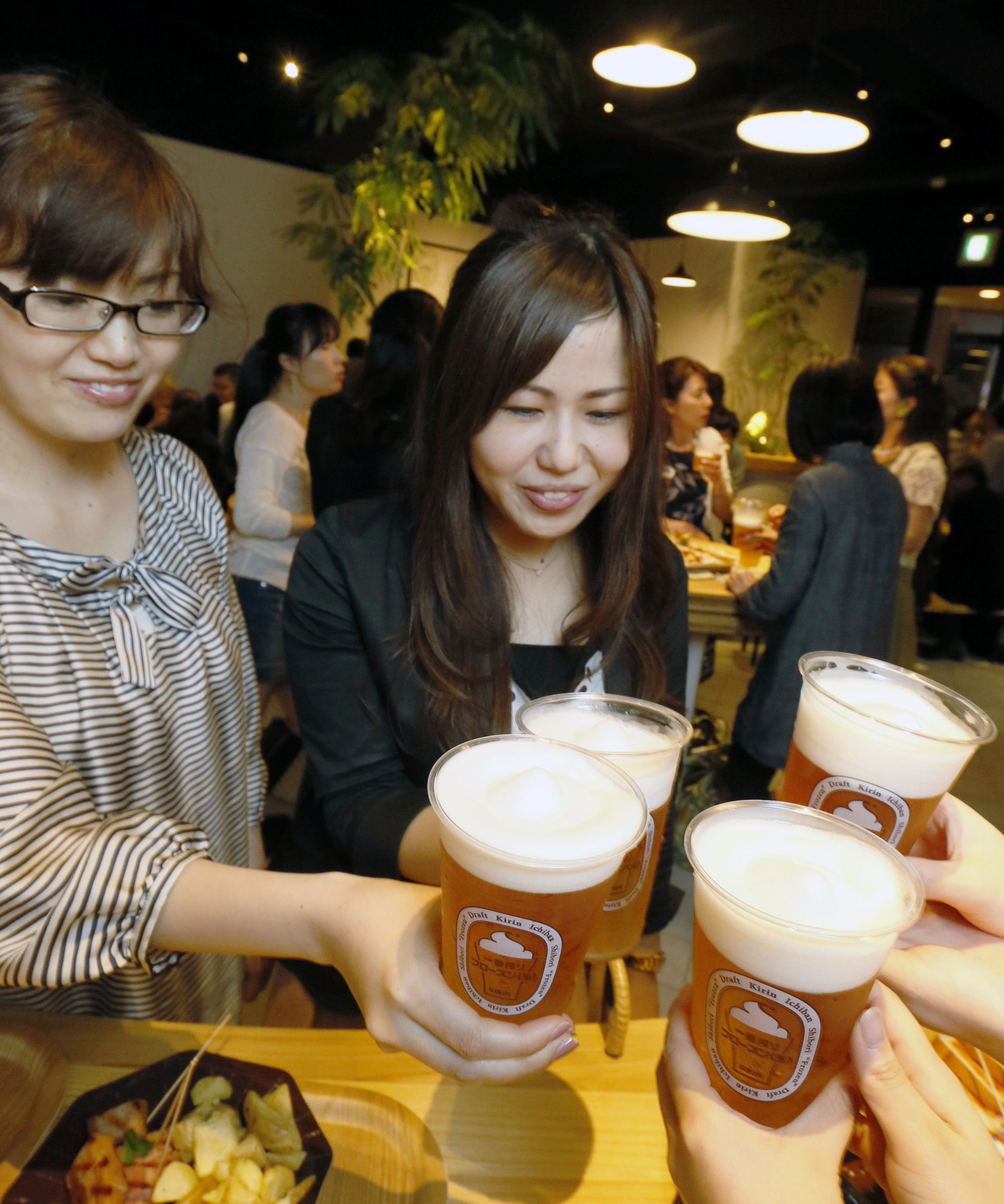 Froth frost: Women drink a new type of beer whose foam is served frozen at a restaurant in the city of Fukuoka on June 29. | KYODO