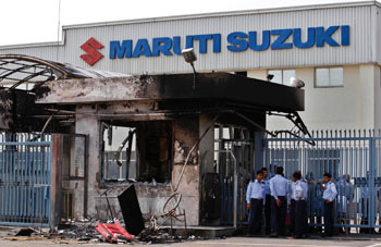 Failure to communicate: Security guards stand near a gutted reception area at the Maruti Suzuki India Ltd. plant in Manesar, southwest of New Delhi, on Thursday. | AP