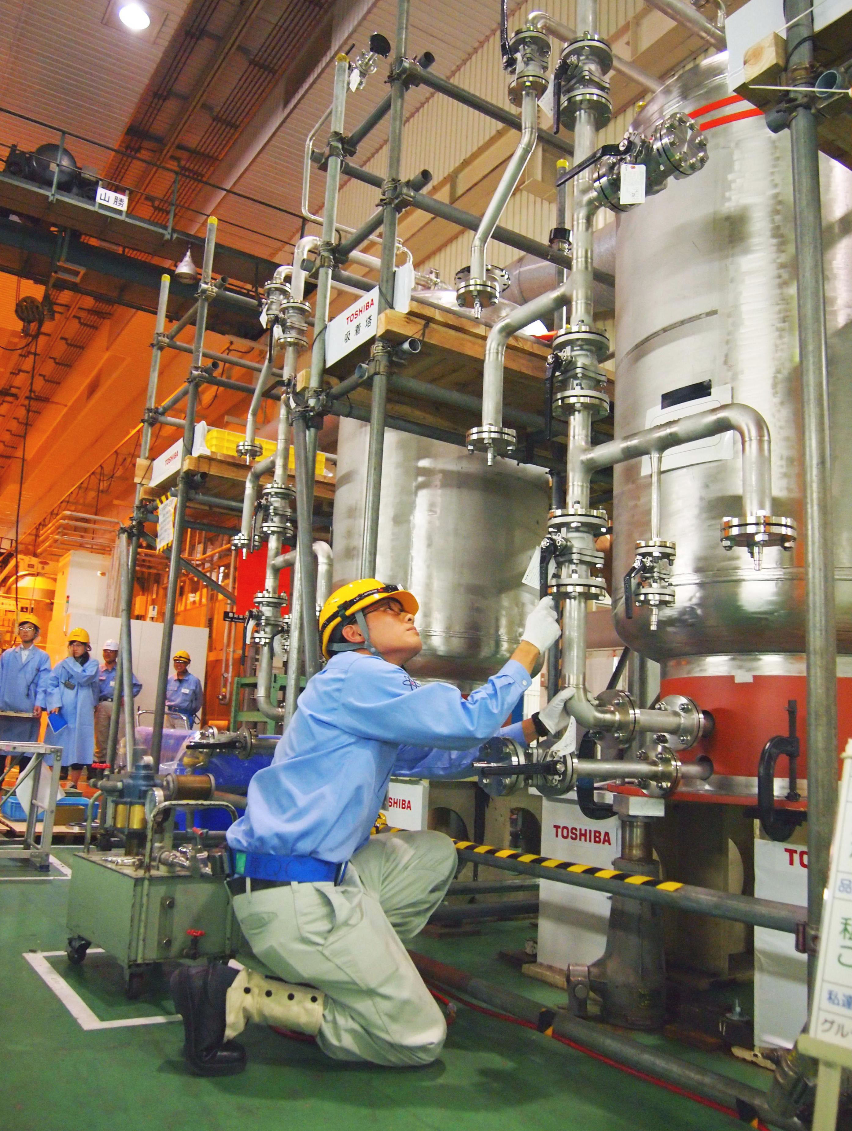 In the pipeline: A nuclear worker checks a new Toshiba Corp. system that can remove radioactive materials from water during a demonstration Tuesday in Yokohama. | KYODO