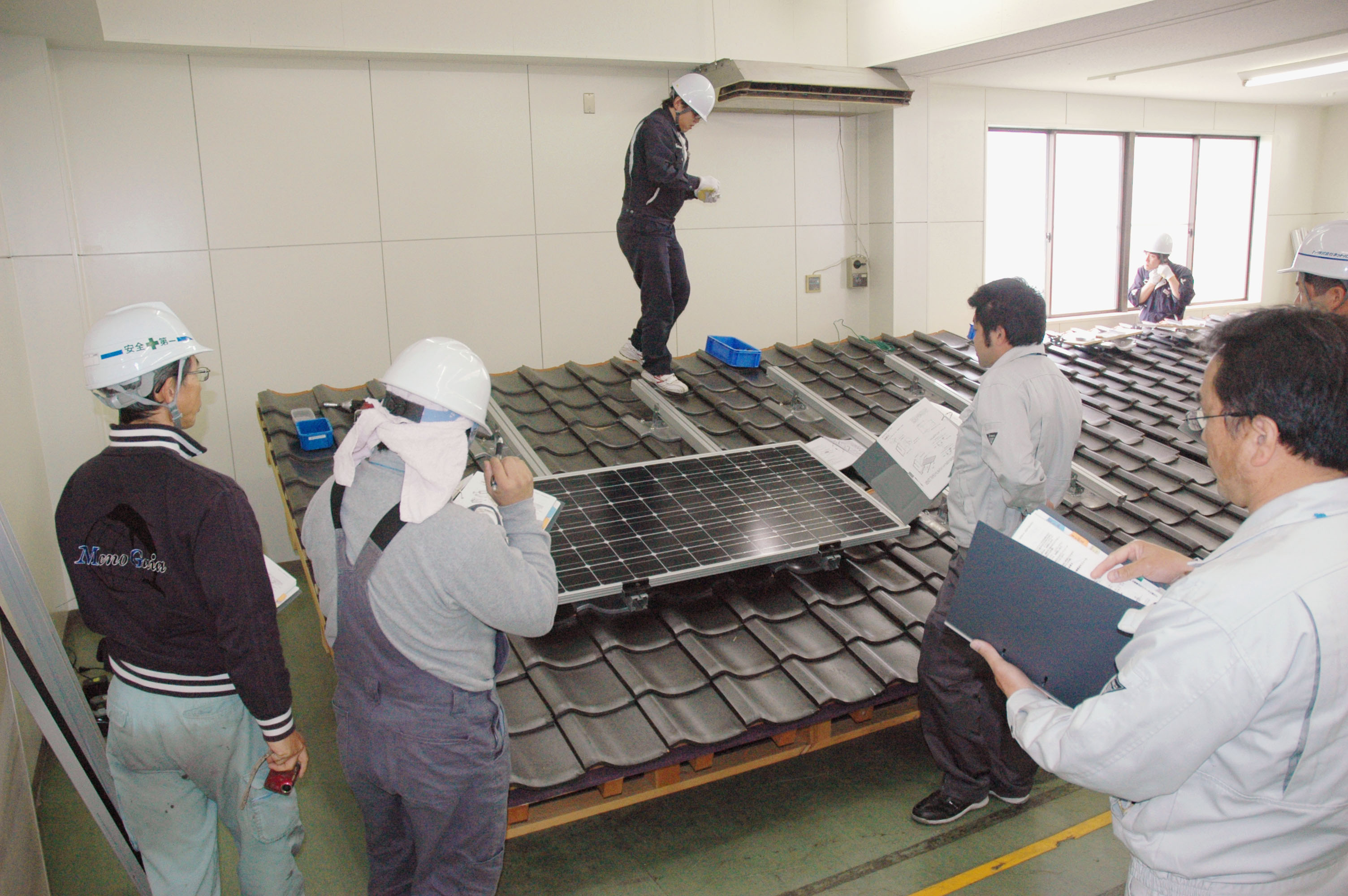 Going solar: Workers undergo training to set up a Chinese-made solar panel on a mock roof at a factory of Suntech Power Japan Corp. in Saku, Nagano Prefecture, in May. | KYODO