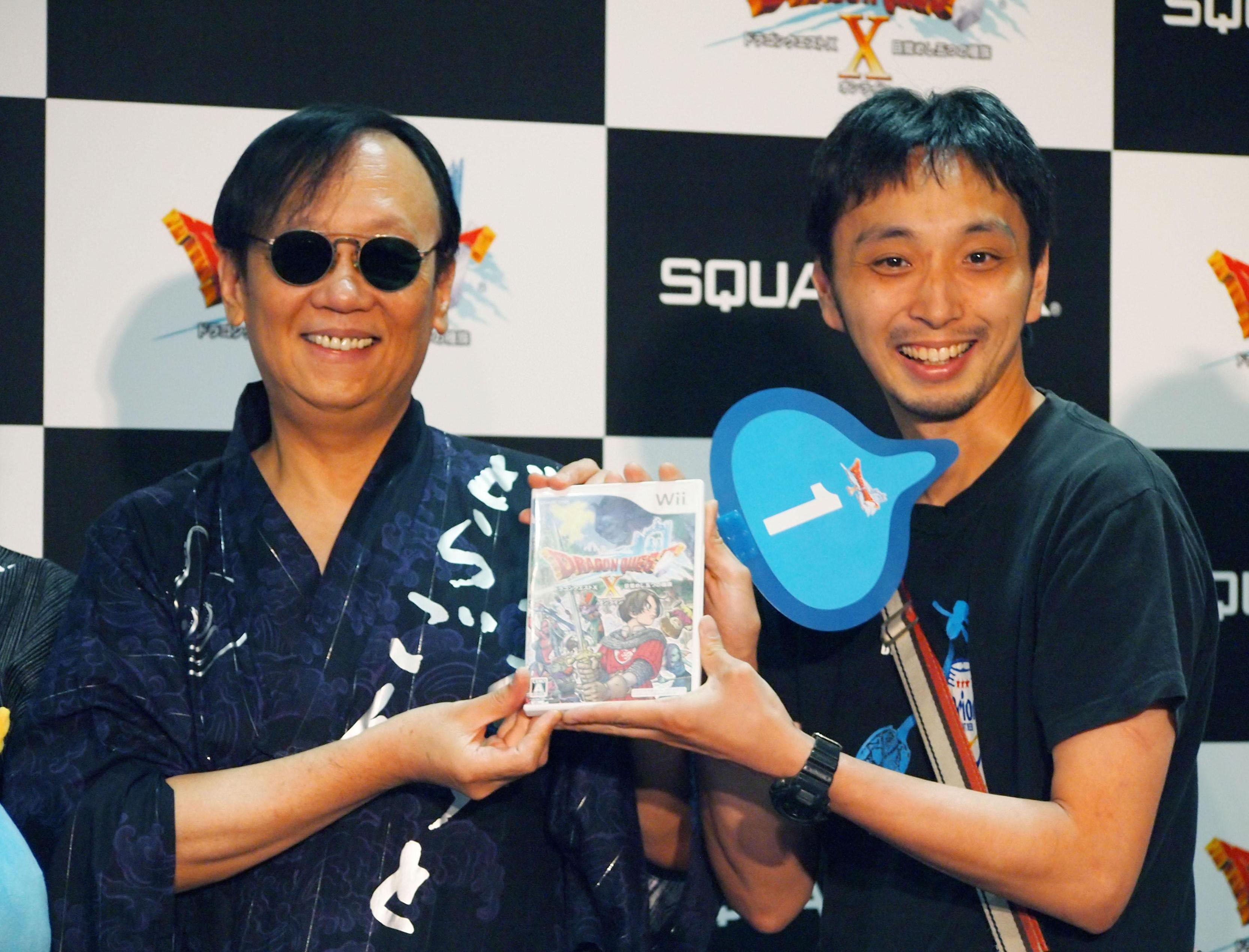 Quest fulfilled:  Yuji Horii (left), creator of the popular 'Dragon Quest' series of video games, hands Kensuke Matayoshi the latest version, which hit the market  Thursday. Matayoshi was first in line at the  Tsutaya book and game store in Shibuya Ward,  Tokyo, when it began selling the game  Thursday morning. | KYODO