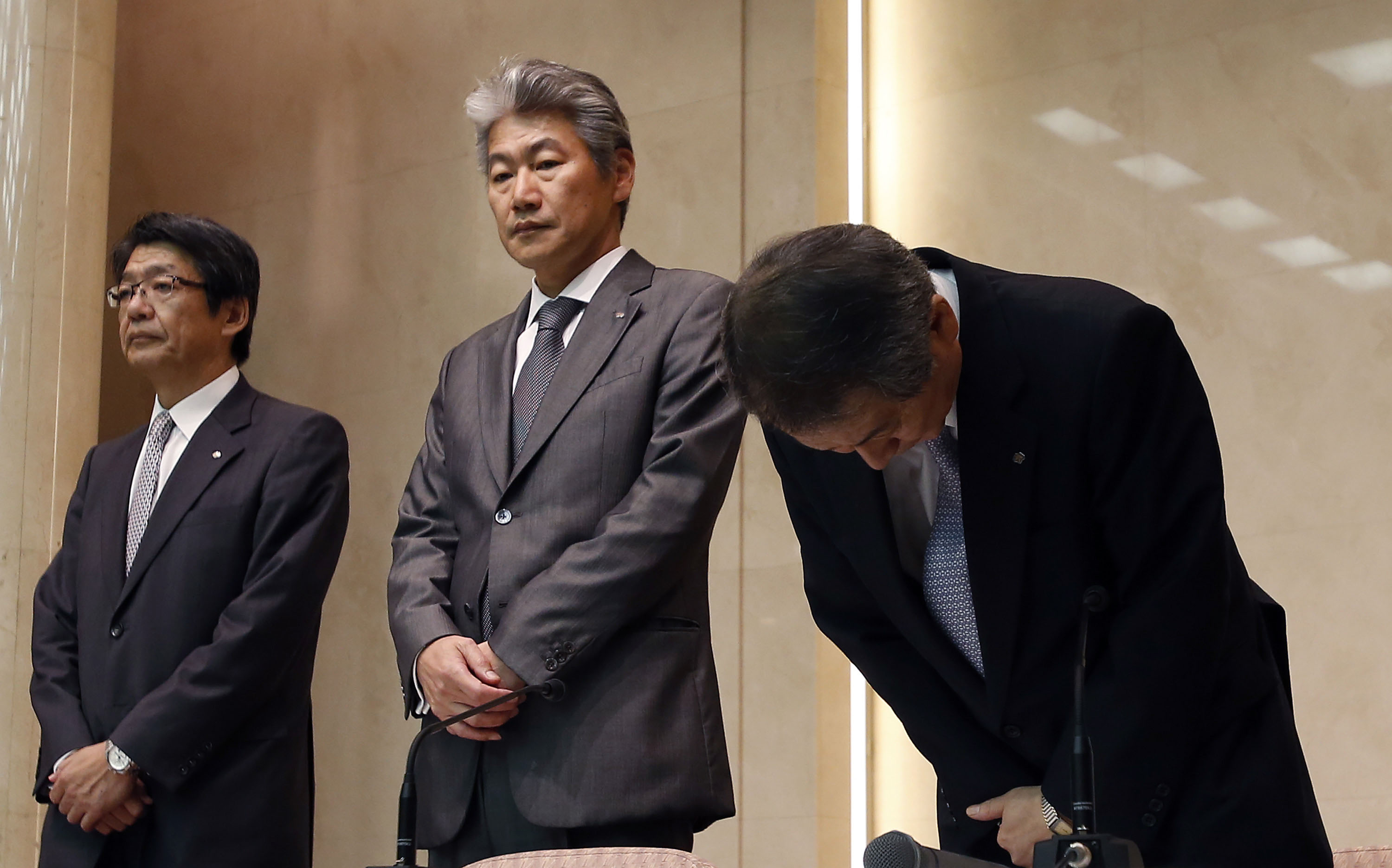 New beginning: Nomura Holdings Ltd. CEO Kenichi Watanabe bows next to Nomura Securities Co. President Koji Nagai (center) and Senior Managing Director Shoichi Nagamatsu at the start of a news conference in Tokyo on July 26. | AP