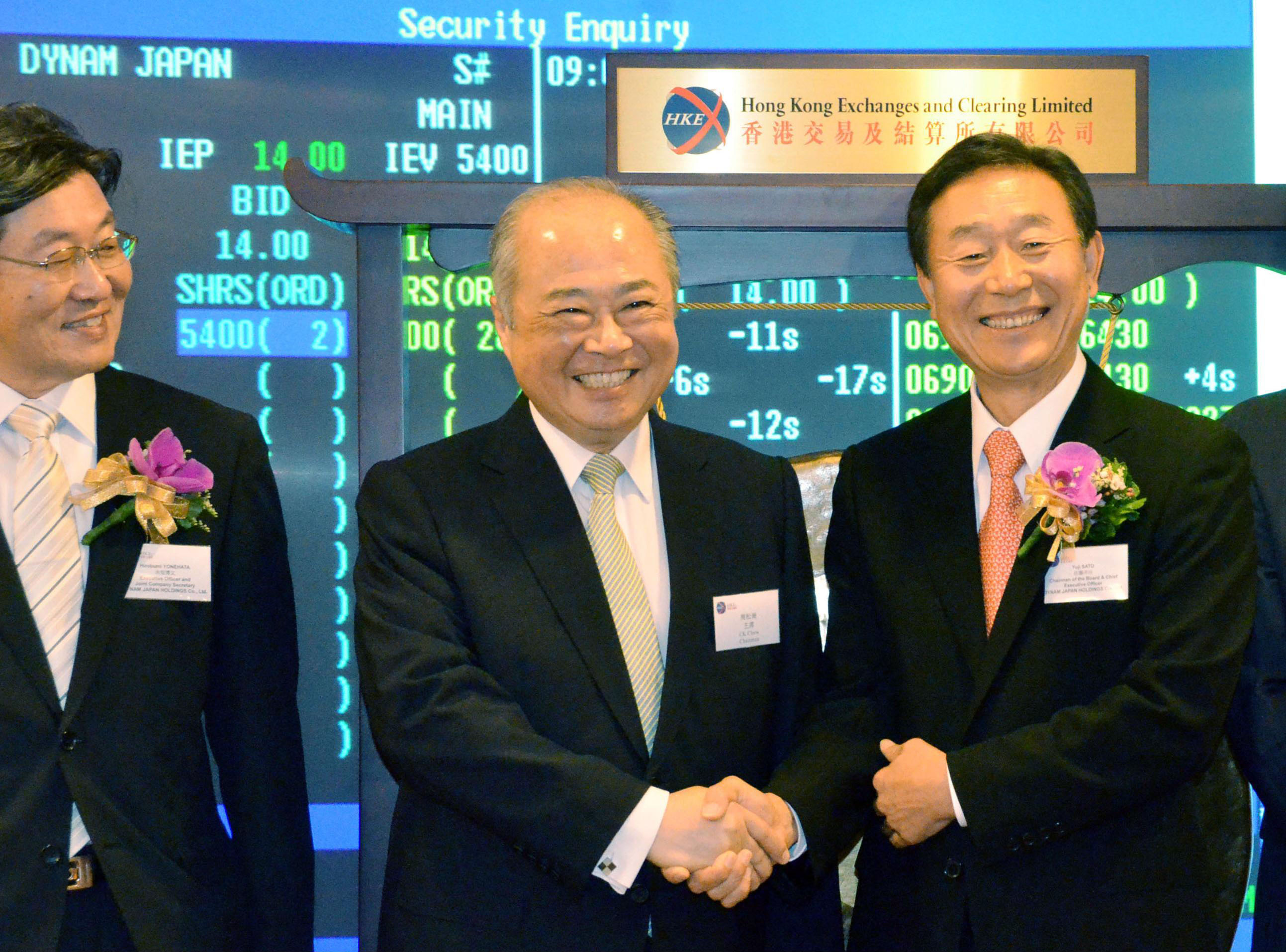 Game of chance: Dynam Japan Holdings Co. President Yoji Sato (right) shakes hands at the Hong Kong Stock Exchange with its chairman, Chow Chung-kong, on Monday. | KYODO
