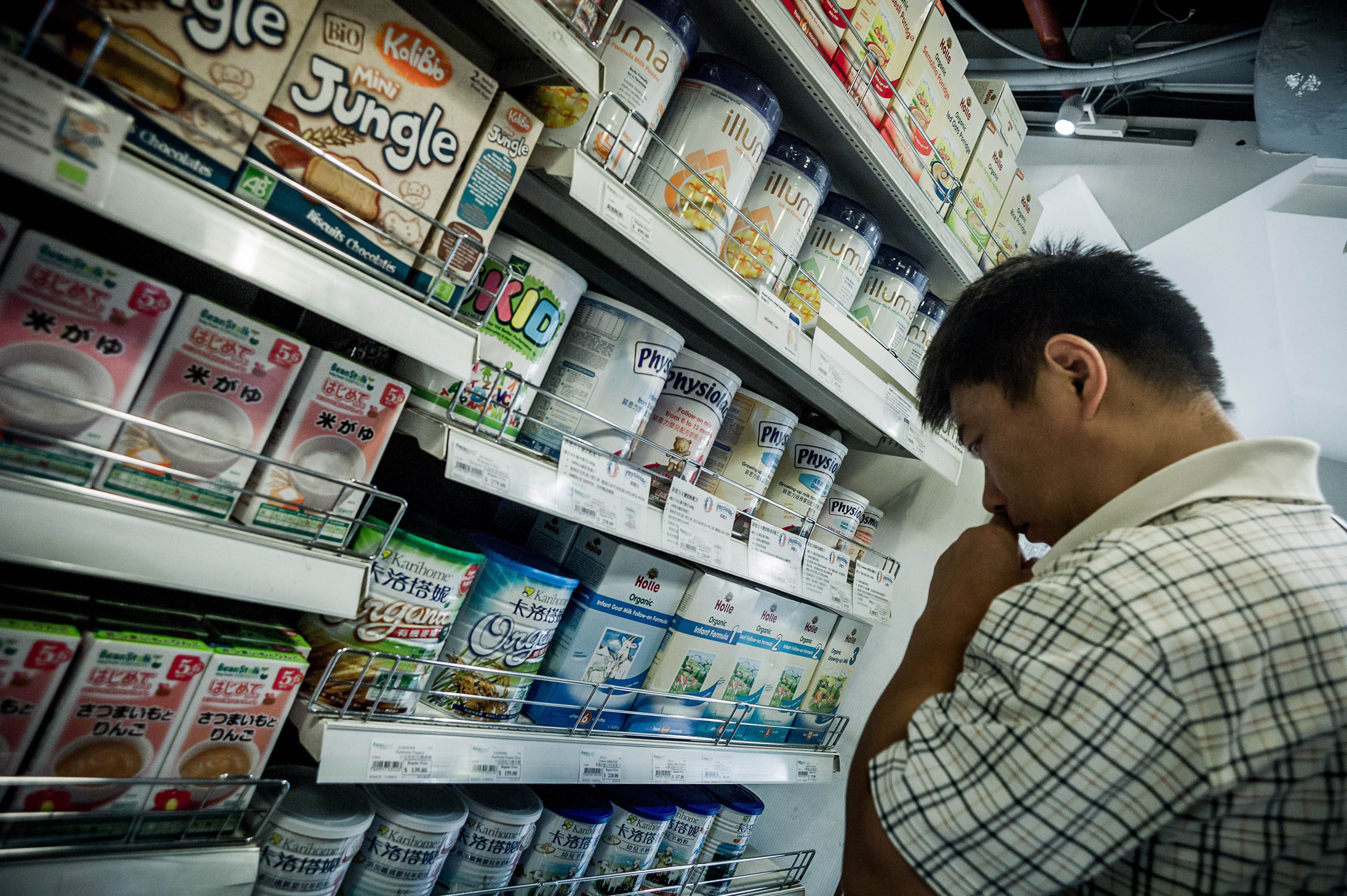 Doubts: A man looks at infant formula in one of Hong Kong's largest Japanese-style department stores Thursday. | AFP-JIJI