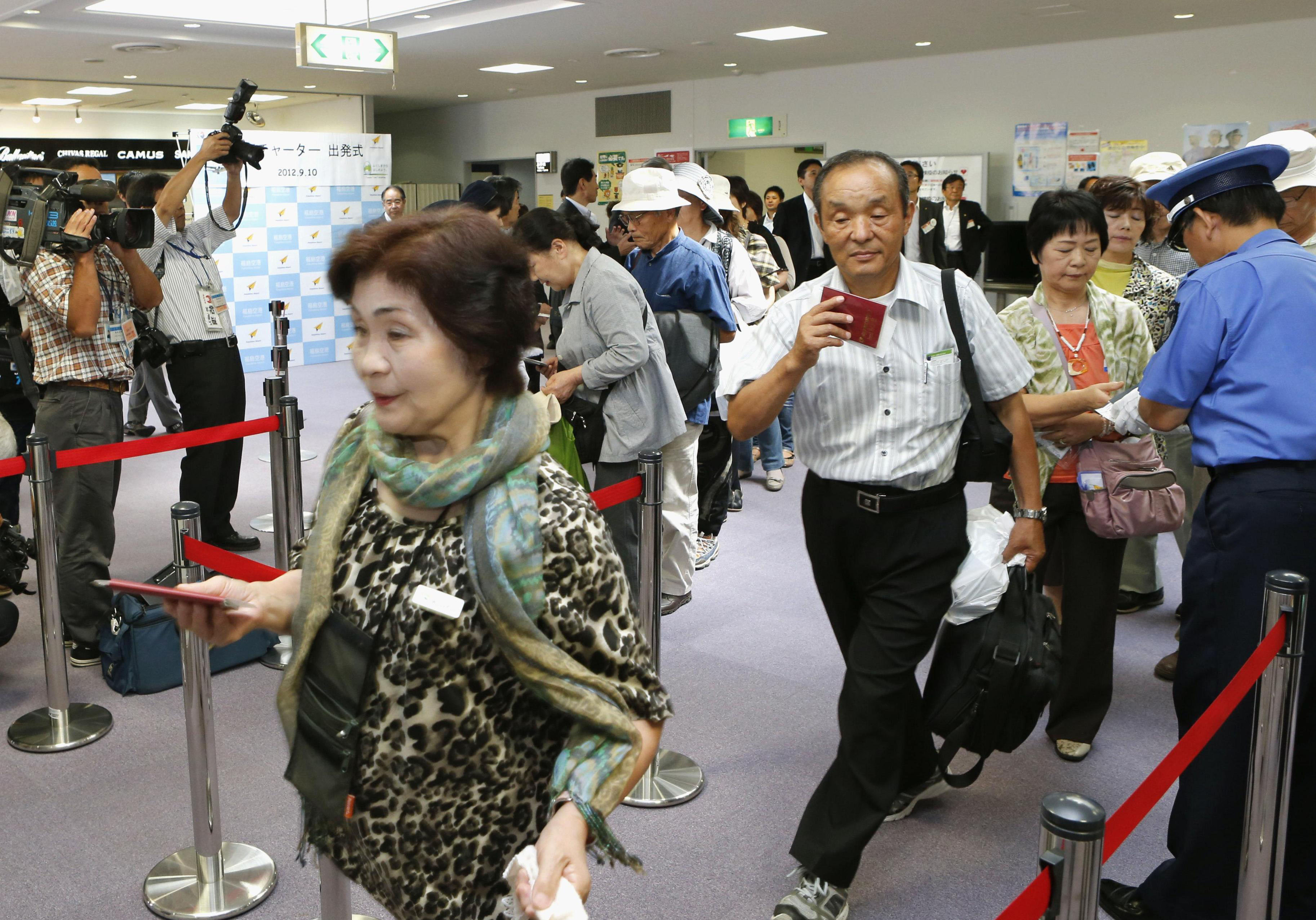 Climbing back: Passengers prepare Monday to board a China Eastern Airlines chartered flight bound for Shanghai at Fukushima Airport, which resumed international services for the first time since the March 2011 disasters. | KYODO