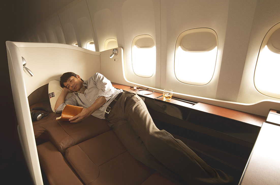 Horizontal flight: A model reads a book while lying down on Japan Airlines Co.'s new first class seat.  The airline plans to begin installing the fully reclining model starting in January. | JAPAN AIRLINES CO.