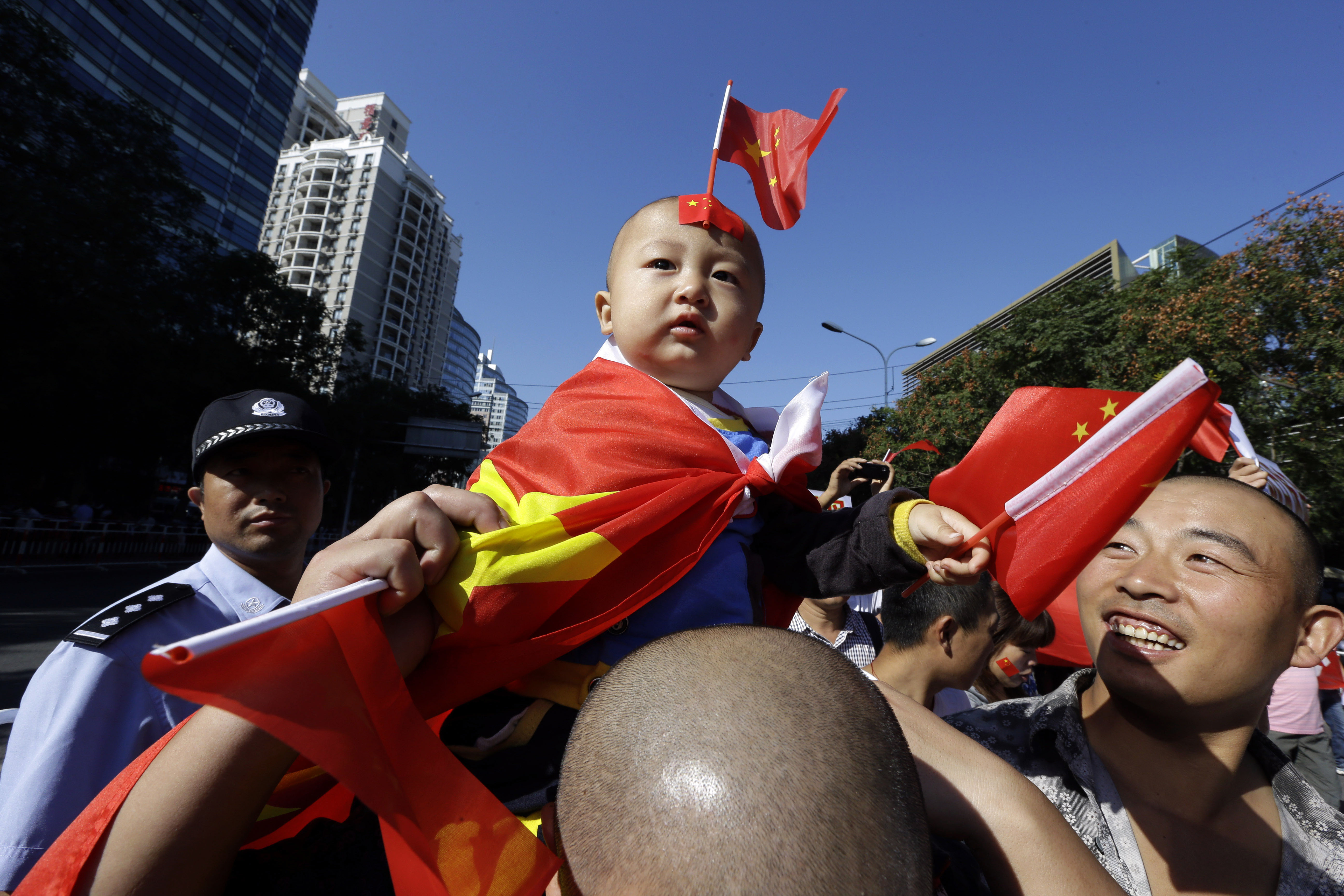 My country: A young boy with a Chinese flag draped over his shoulders and a miniature one stuck to his forehead sits on a man's shoulders during a protest near the Japanese Embassy in Beijing on Tuesday. | AP