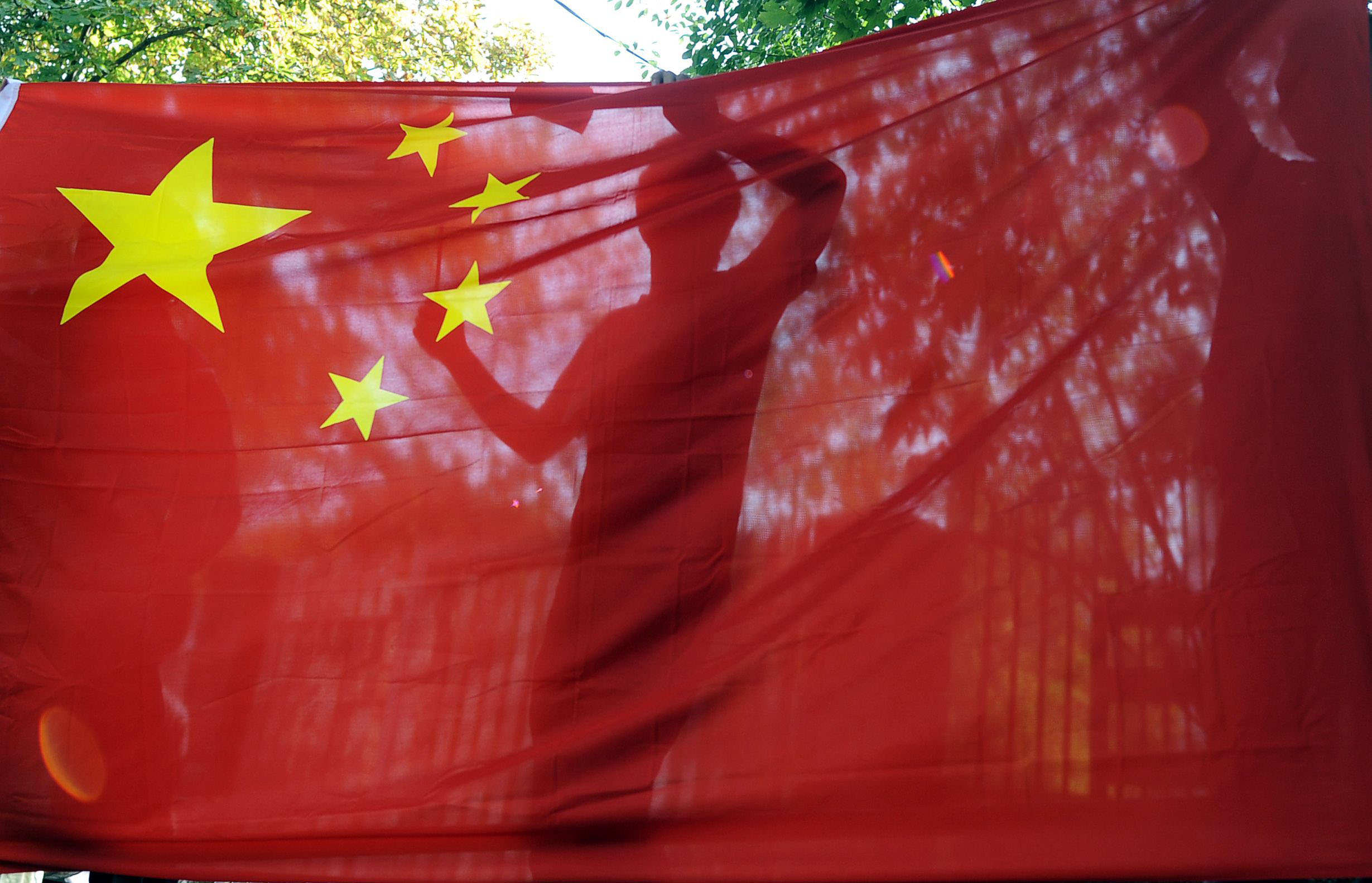 Global reach: A demonstrator is silhouetted against a Chinese flag at the Japanese Embassy in Budapest on Monday during a protest over the Senkaku Islands dispute. | AFP-JIJI