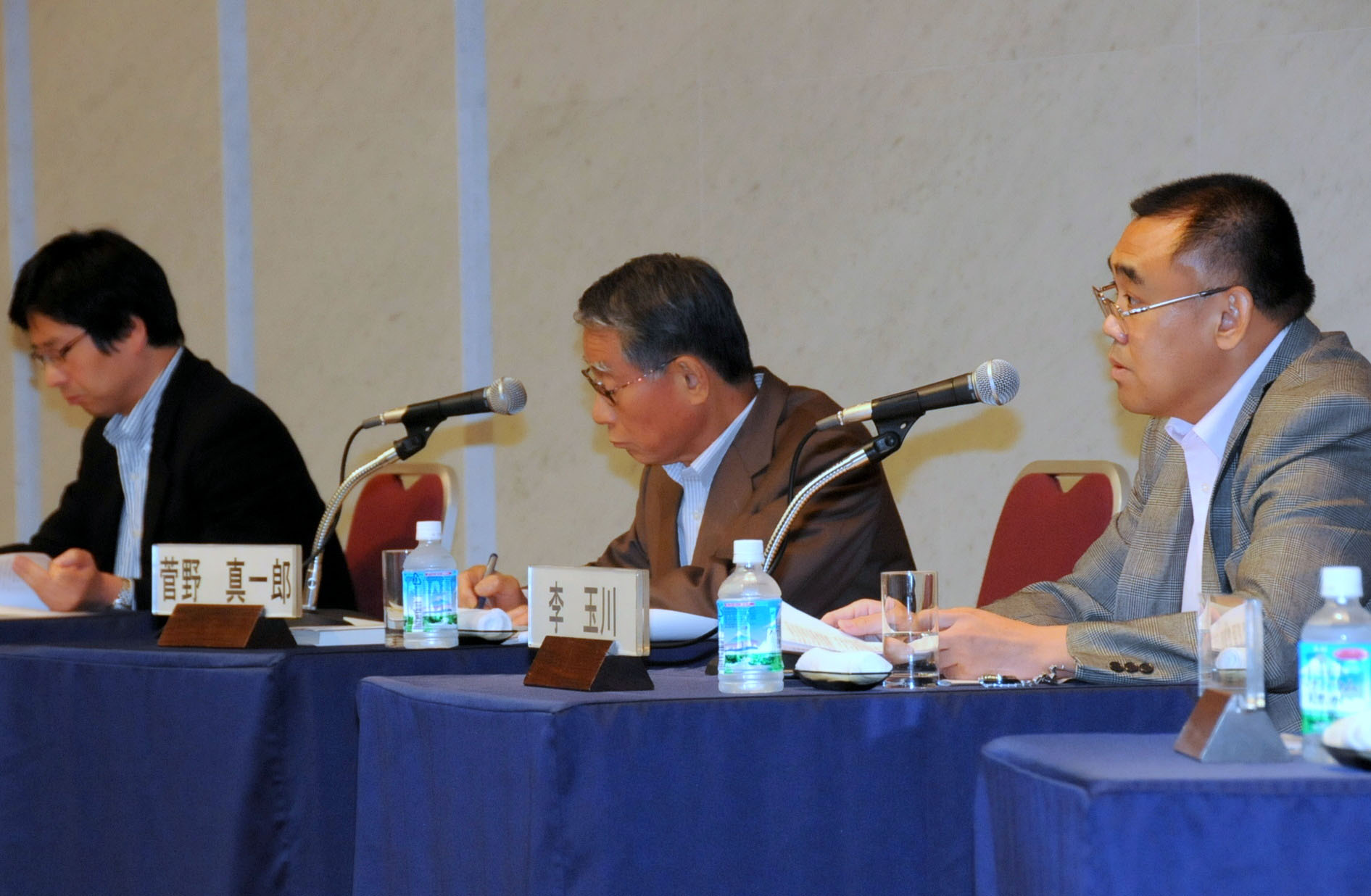 Li Yuchuan (right), Tokyo bureau chief of the Beijing Daily, speaks during the Aug. 29 symposium at Keidanren Kaikan in Tokyo, while Liu Jie (left), a professor at Waseda University's Faculty of Social Sciences, and Shinichiro Kanno, an adviser to Mizuho Corporate Bank, listen. | SATOKO KAWASAKI