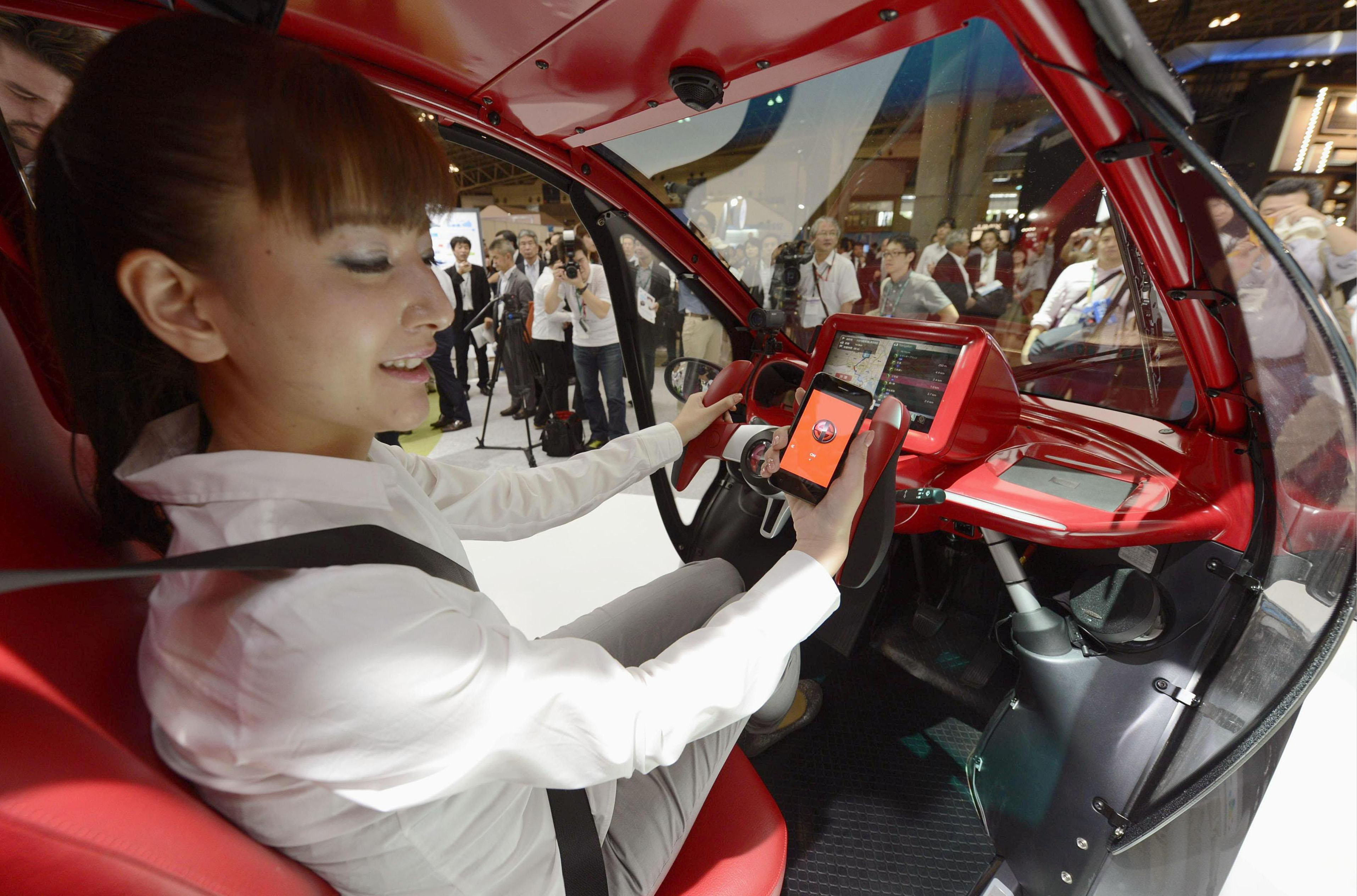 The new bug:  Toyota Motor Corp.'s Smart Insect single-occupant electric vehicle is displayed at the CEATEC-Japan exhibition  at the Makuhari Messe convention center in Chiba Prefecture on Tuesday. | KYODO