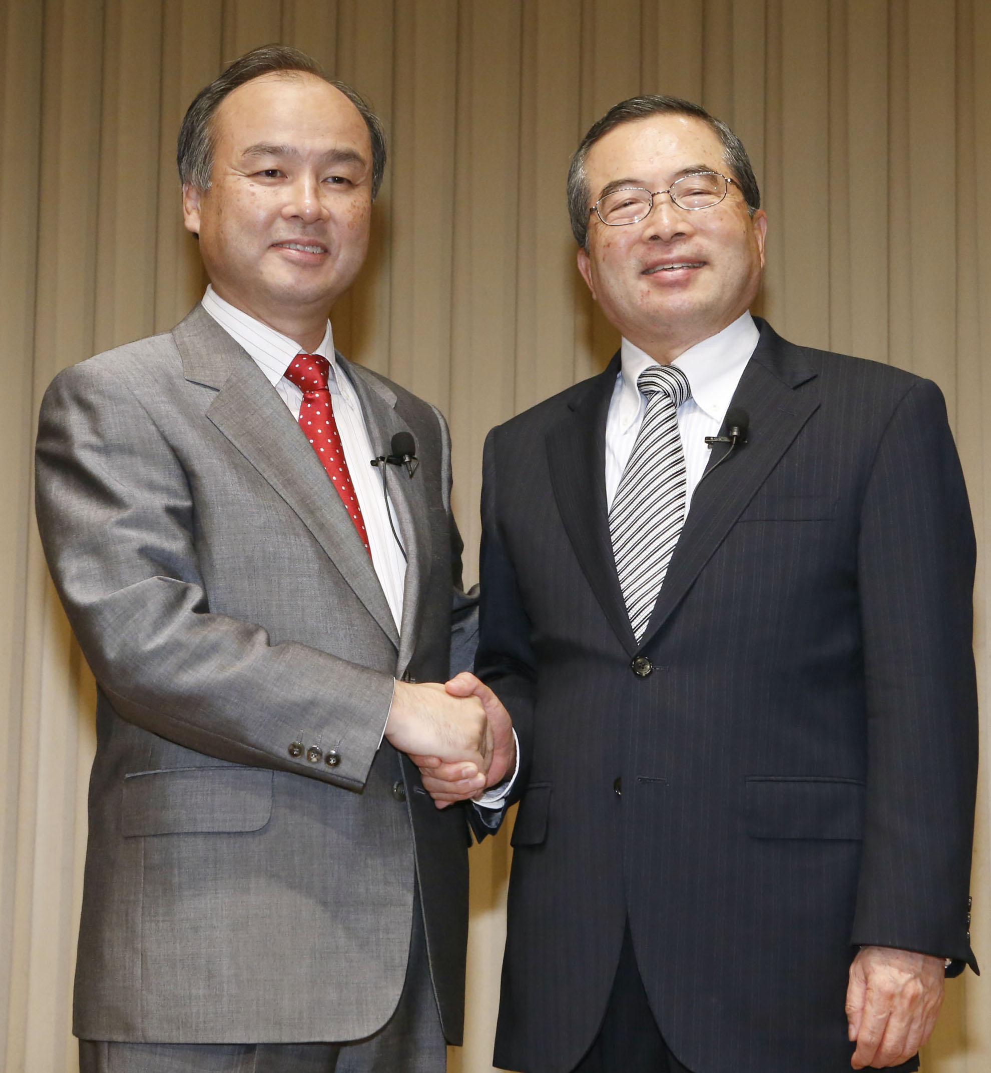 Hot line: Softbank Corp.'s acquisition of eAccess Ltd. is announced by Softbank CEO Masayoshi Son (left) and eAccess Ltd. Chairman Sachio Senmoto at a news conference Sept. 1 in Tokyo. The release of Apple Inc.'s iPhone 5 handset is behind Softbank's move to expand its infrastructure. | KYODO