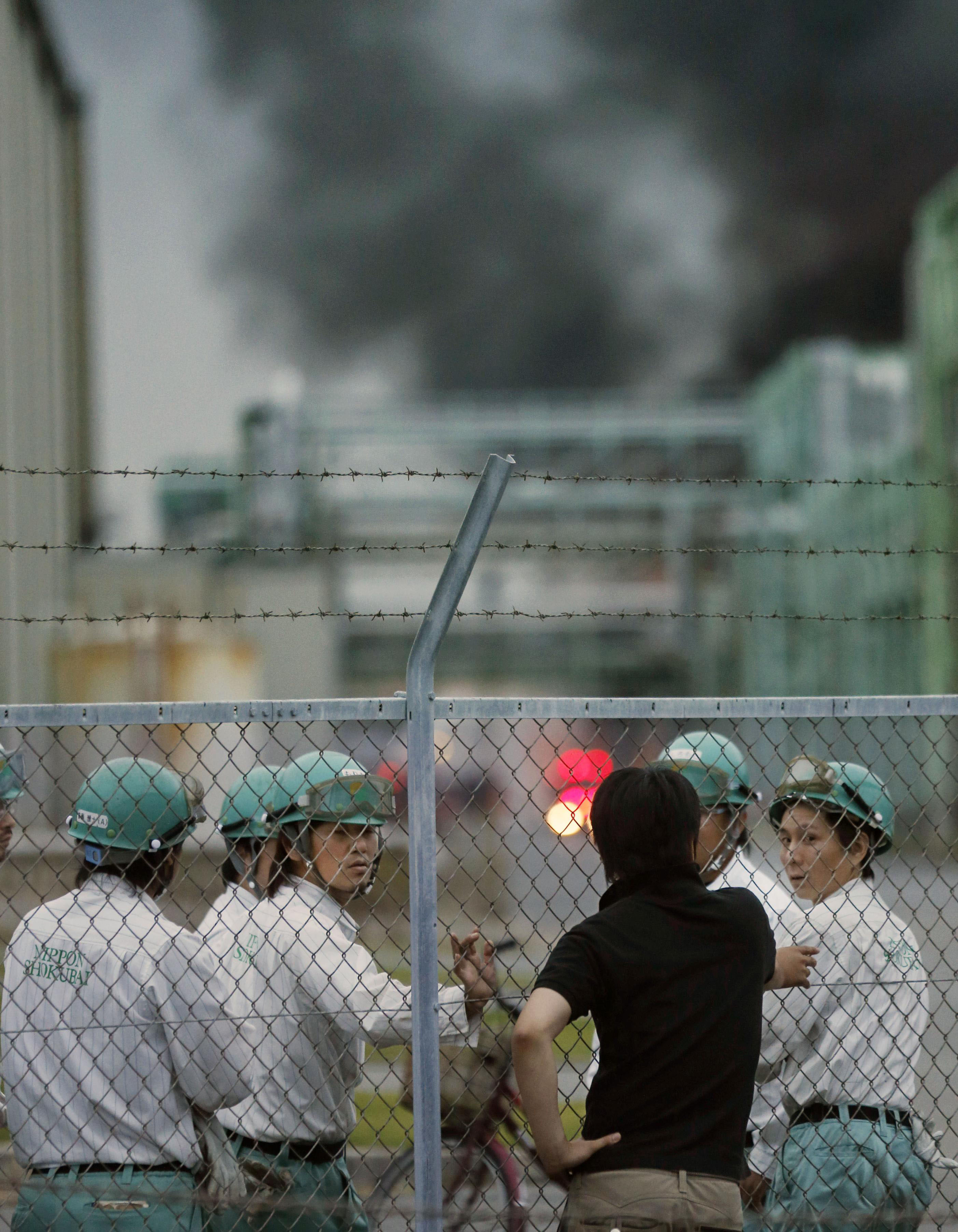 Break time: Workers stand by while a fire burns in the Nippon Shokubai Co. chemical plant in Himeji, Hyogo Prefecture, on Sept. 29. | KYODO