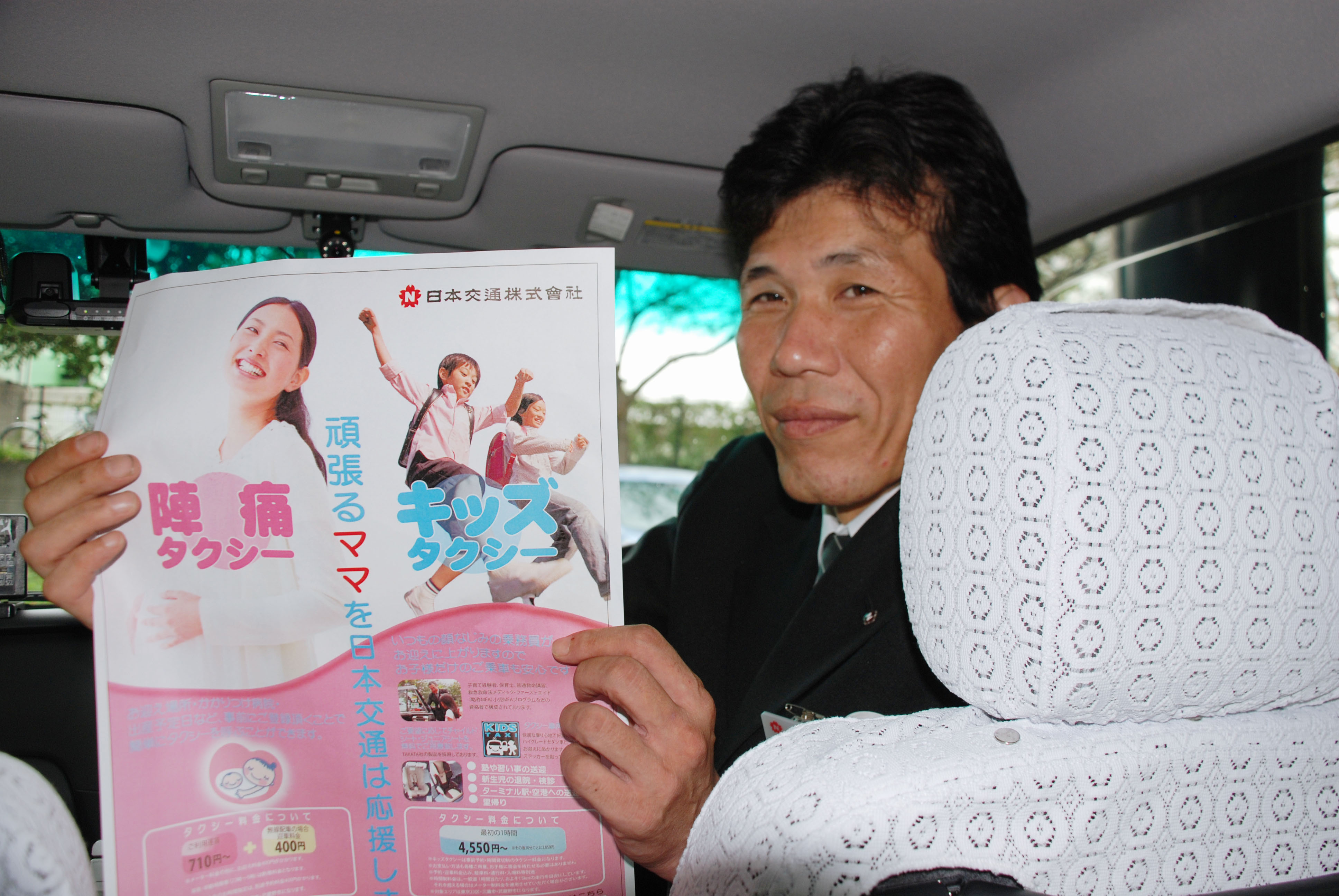 Always in hailing distance: A Nihon Kotsu Co. taxi driver holds up a pamphlet explaining the company's around-the-clock service to take women who have gone into labor to the hospital. | KYODO