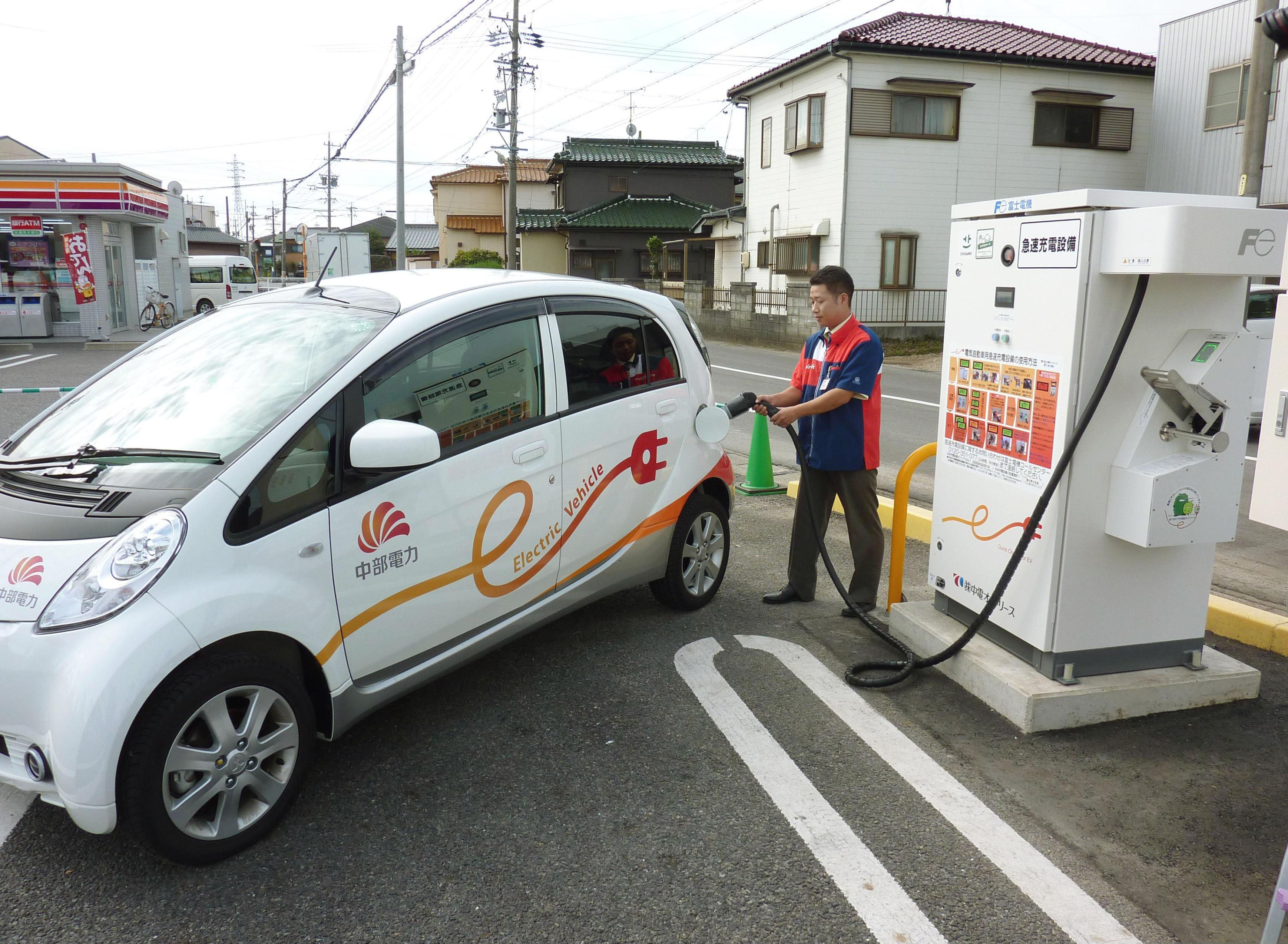 Charge it: A Chubu Electric Power Co. official shows how to use a rapid battery charger for electric vehicles Thursday at a Circle K convenience store in Komaki, Aichi Prefecture. | KYODO
