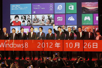 In with the new: Microsoft Co. Japan CEO Yasuyuki Higuchi (fifth from left) and executives of various PC makers celebrate the debut of Windows 8, Microsoft's latest operating system, in Tokyo's Akihabara district Friday. | KYODO