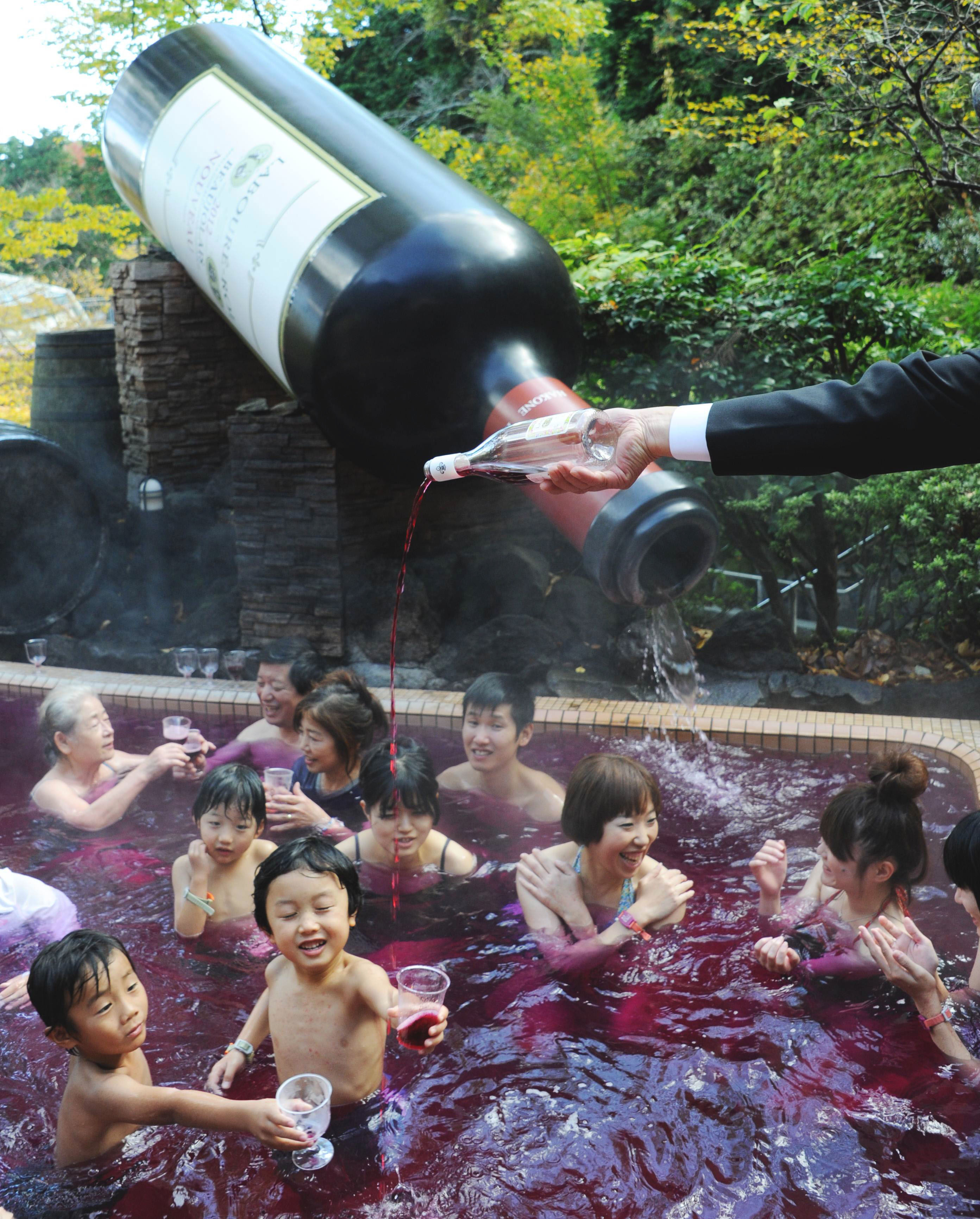 'Sante': Sommelier Shunji Kanaya pours 2012 Beaujolais Nouveau into a 'wine spa' at the Hakone Kowakien Yunessun hot springs resort in Hakone, Kanagawa Prefecture, on Thursday. | AFP-JIJI