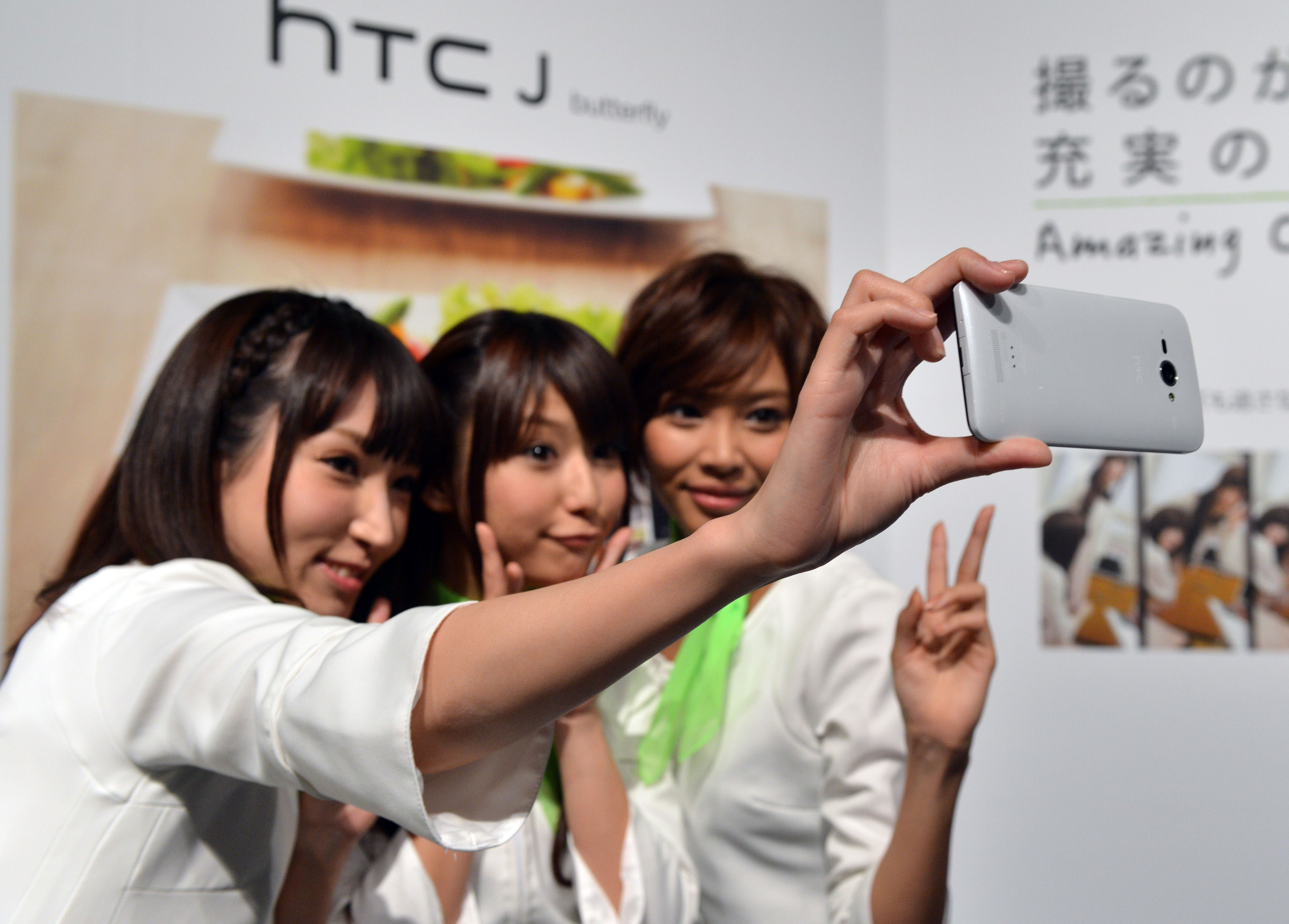 All in one: Models take a self-portrait with a new 8-megapixel camera/smartphone called the HTC J butterfly, produced by Taiwanese electronics maker HTC, in Tokyo on Nov. 20. The soaring popularity of smartphones is crushing demand for point-and-shoot cameras as territorial disputes put pressure on sales. | AFP-JIJI