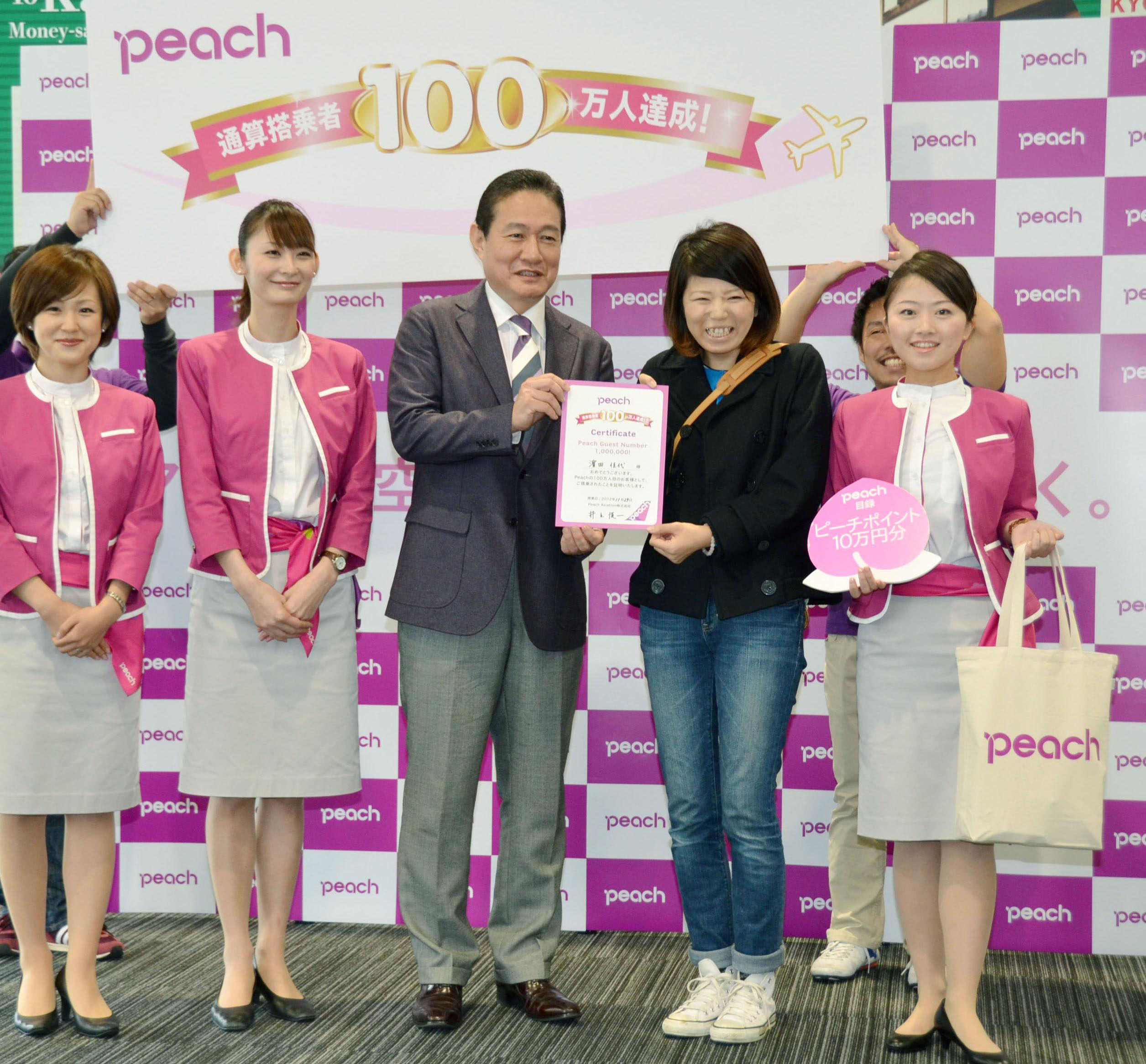 Milestone: Peach Aviation CEO Shinichi Inoue poses Thursday with the budget airline's 1 millionth passenger at Kansai International Airport. | KYODO