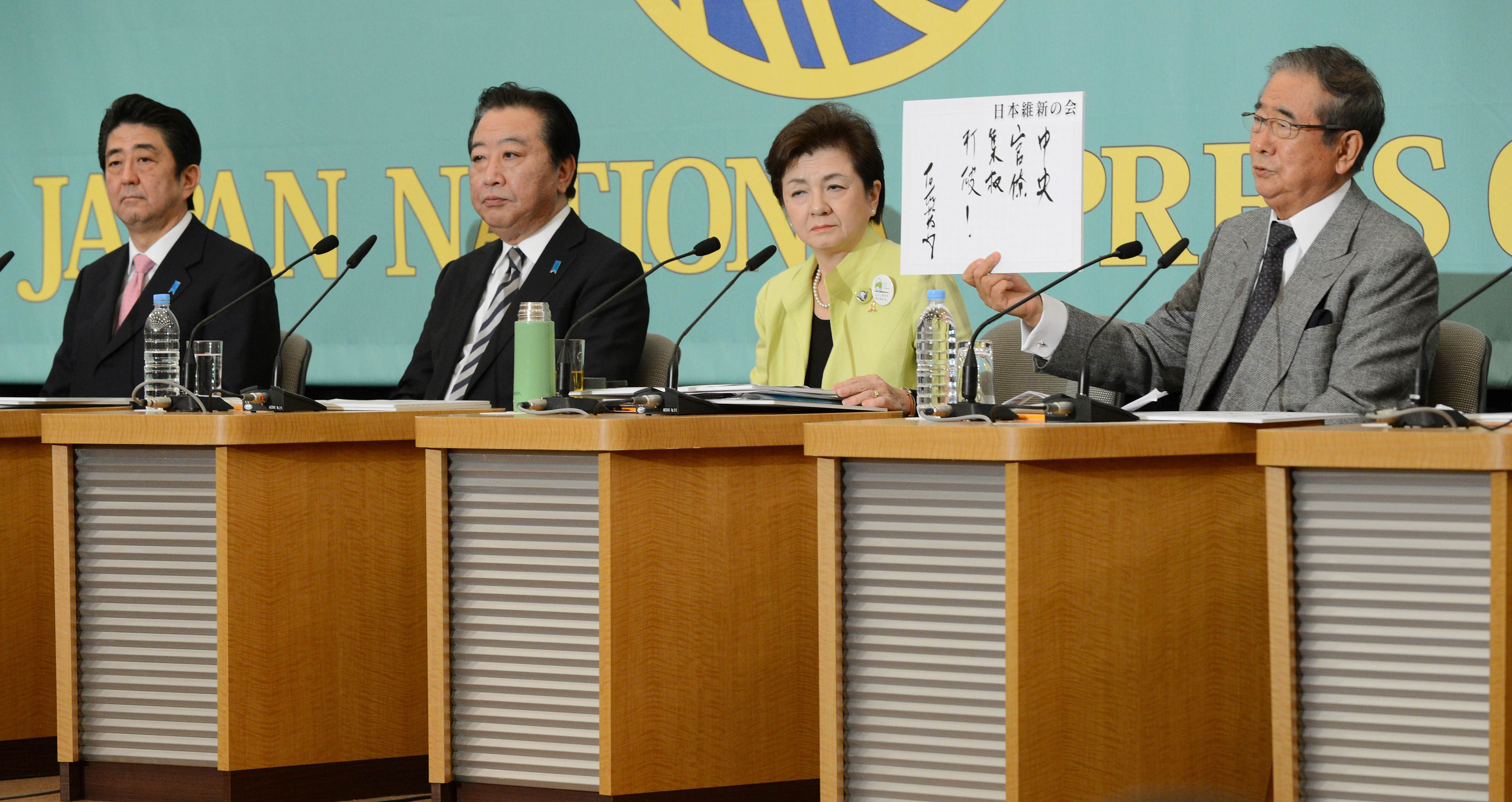 Agreeing to disagree: Nippon Ishin no Kai leader Shintaro Ishihara holds a sign at a debate with 10 other party chiefs at the Japan National Press Club in Tokyo on Friday, including (left to right) Liberal Democratic Party President Shinzo Abe, Democratic Party of Japan leader Yoshihiko Noda and Nippon Mirai no To head Yukiko Kada. | AFP-JIJI