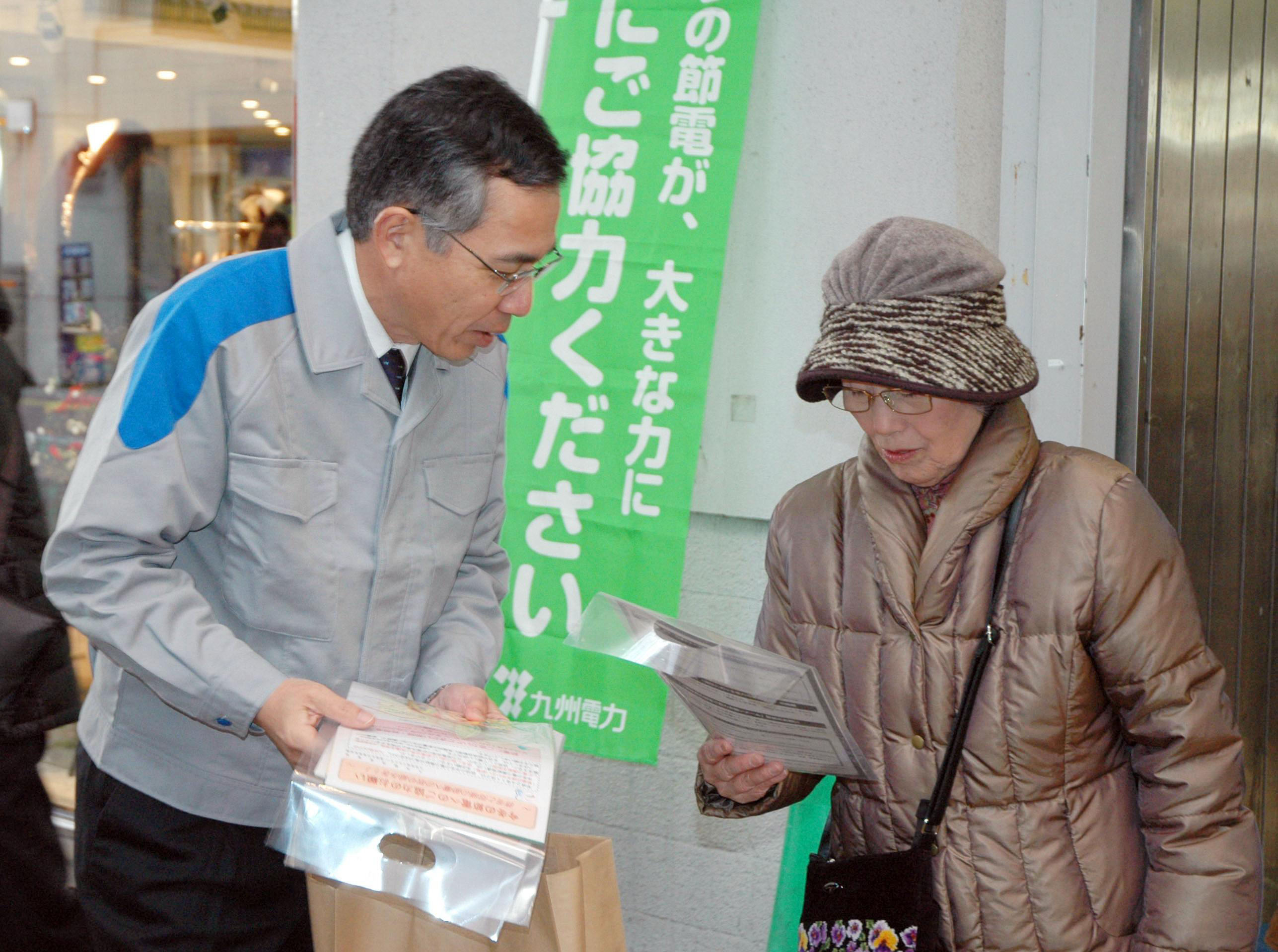 Appeal: An employee of Kyushu Electric Power Co. hands out leaflets asking people to save energy in Fukuoka on Monday.   KYODO