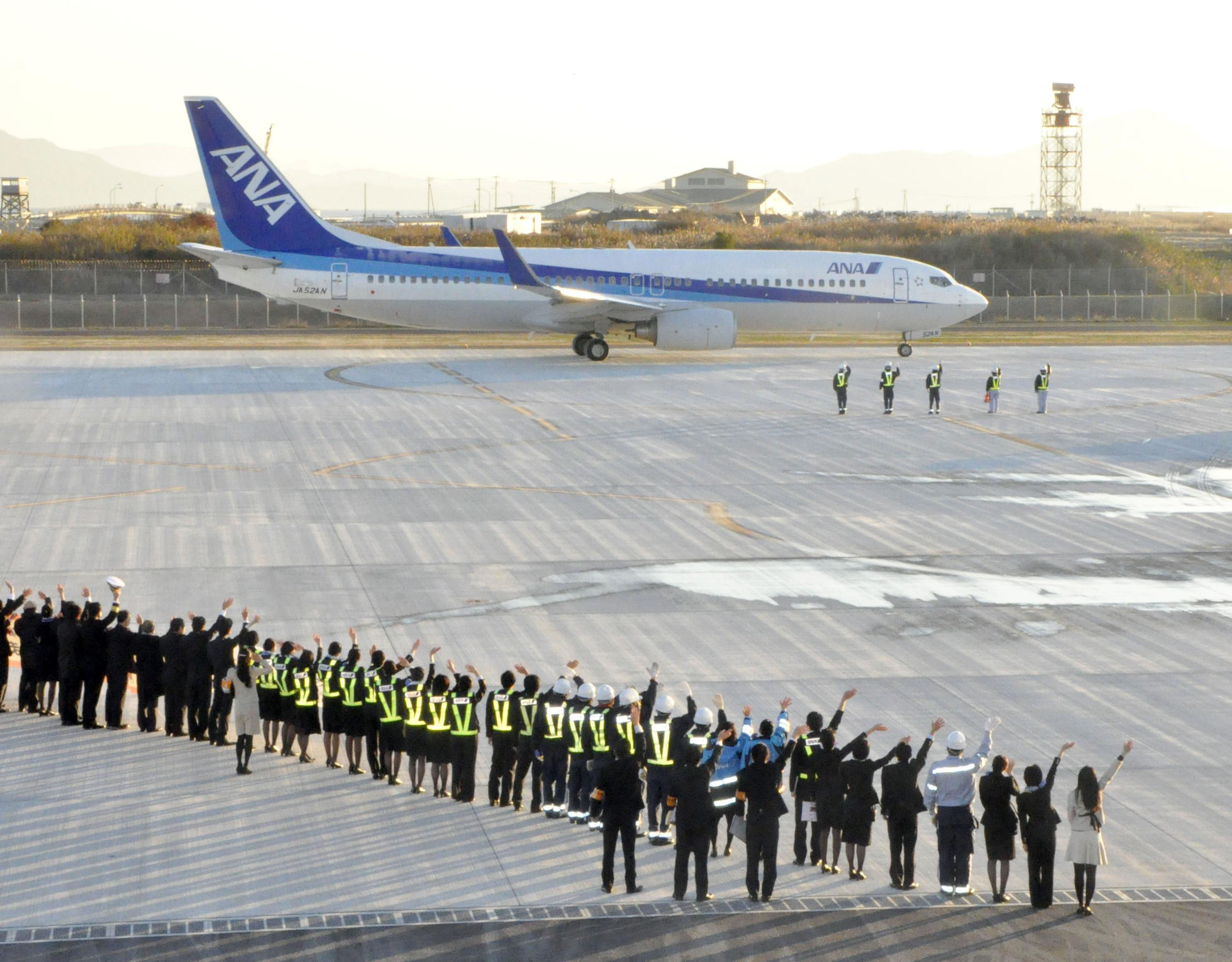 Long time coming: Airline employees and staff at Iwakuni Kintaikyo Airport wave as the facility's first commercial flight in 48 years prepares for takeoff Thursday. | KYODO