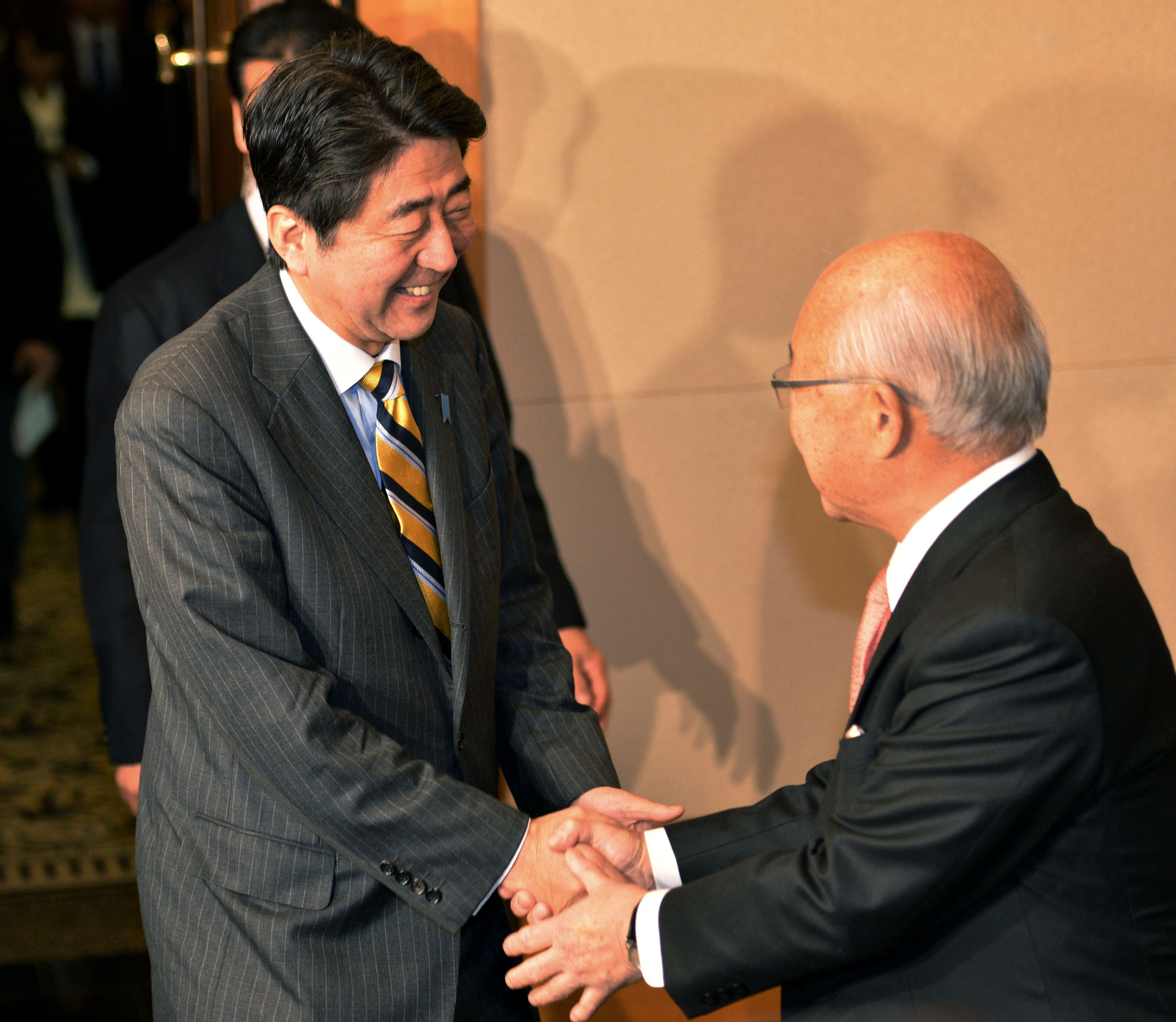 Back in play: Shinzo Abe, the next prime minister, is greeted by Fumiaki Watari, chairman of Keidanren's advisory board, upon his arrival for talks with the nation's top business leaders Tuesday in Tokyo. | AFP-JIJI