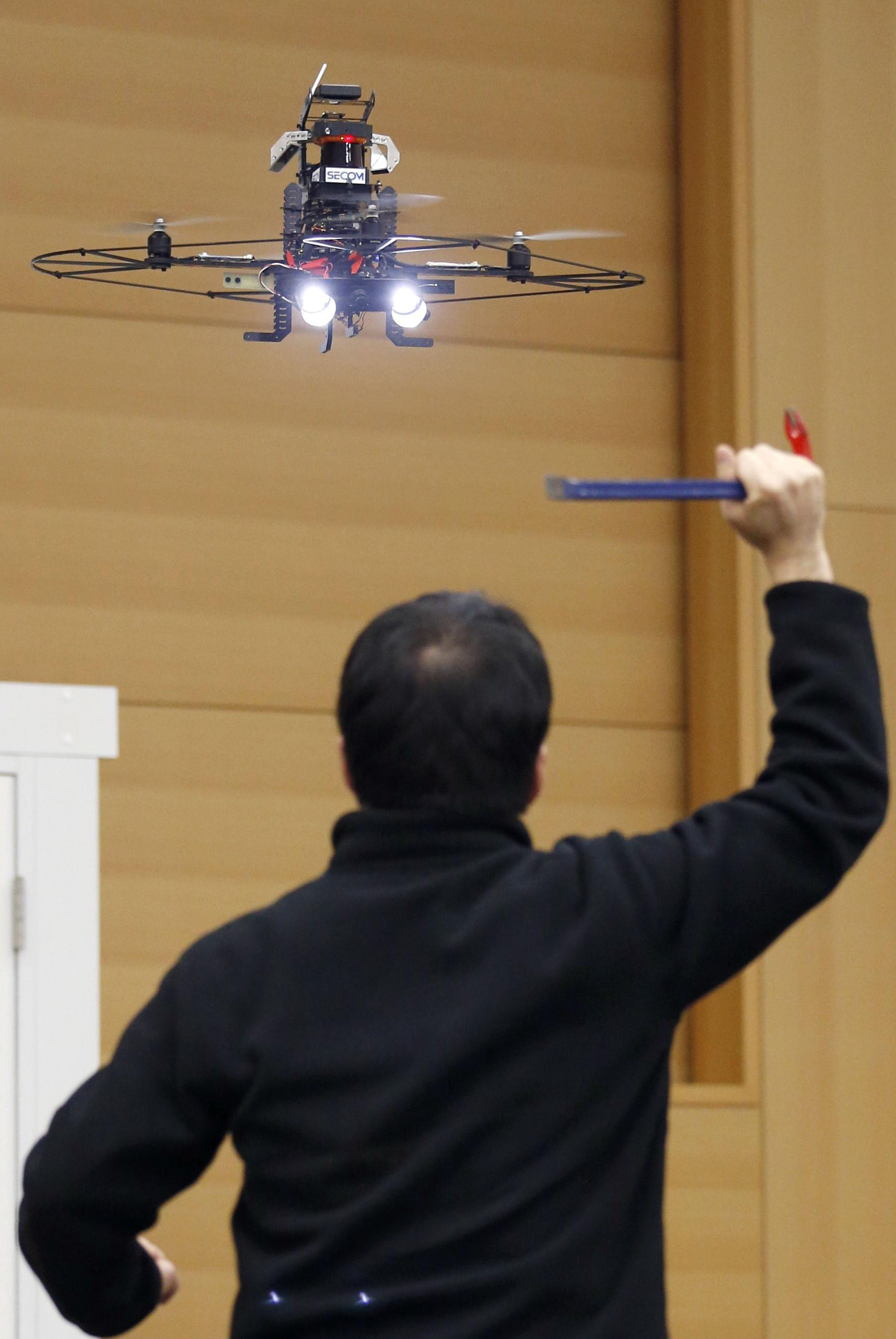 Big brother in Japan: A drone prototype is seen videotaping a man acting as an intruder near a building Wednesday. | KYODO