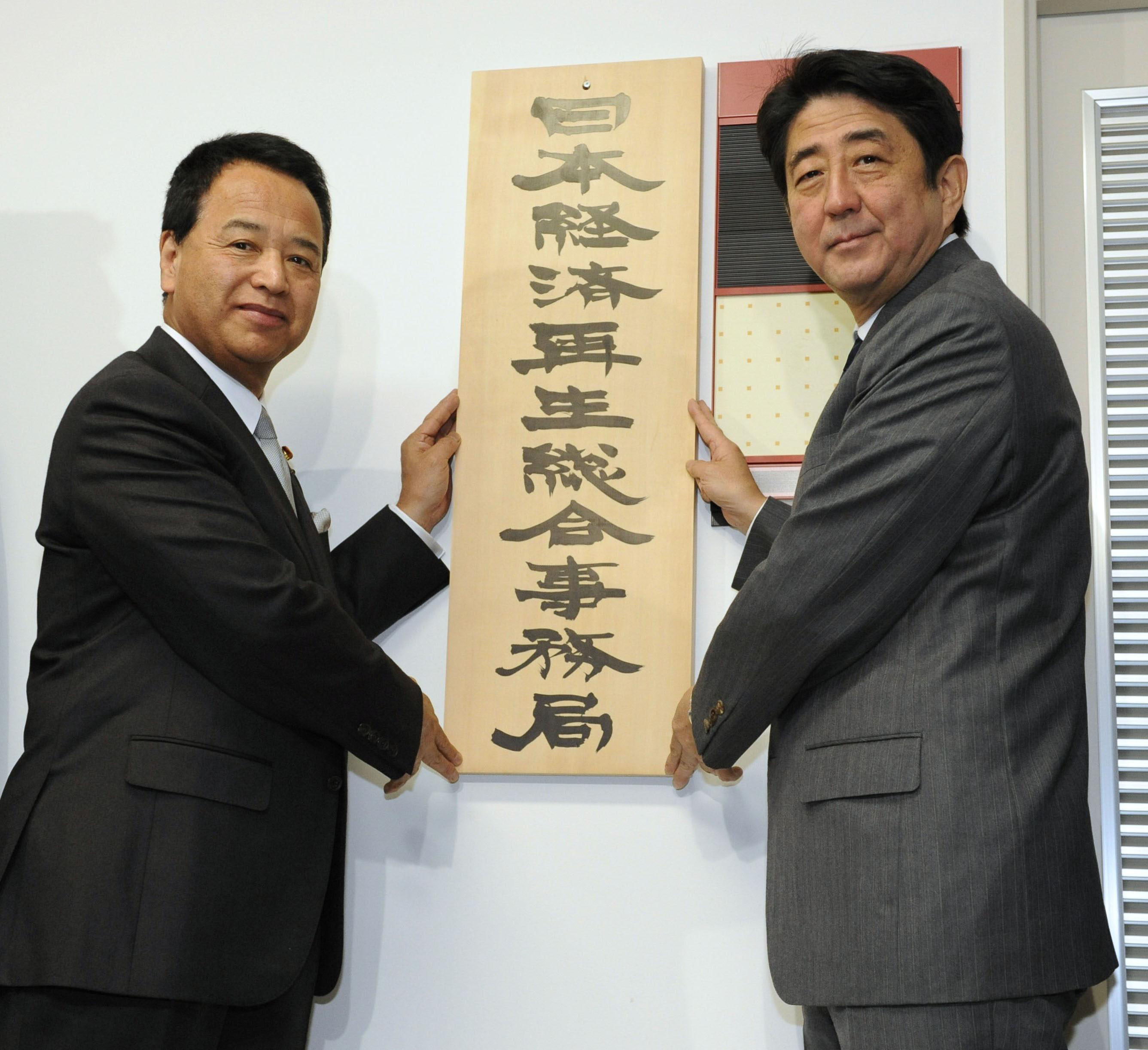 The right props: Prime Minister Shinzo Abe (right) and economic and fiscal policy minister Akira Amari put up a sign Monday for the secretariat of the economic revitalization headquarters at the Cabinet Office. | KYODO