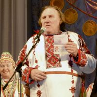 New motherland: French actor Gerard Depardieu poses with his new Russian passport while wearing a traditional folk outfit in the city of Saransk, Russia, on Sunday. | AP