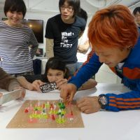 Making ideas come to life: Designer Kota Nezu (right), turns cogs adorned with objects created by participants during a 3-D printing and modeling workshop held recently at the FabCafe in Tokyo's Shibuya district. TOMOKO OTAKE PHOTOS