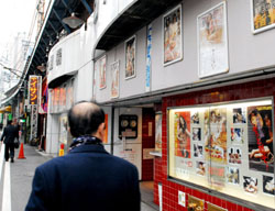 Under the tracks: A man passes a pornographic movie house in Tokyo's Shinbashi district on Dec. 2, 2008. | YOSHIAKI MIURA PHOTO