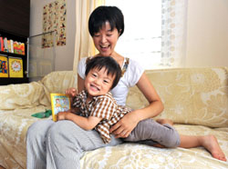 Keeping records: Etsuko Minengo and her 2-year-old son, Tsukasa, look at their Maternal and Child Health Handbook at their home in Tokyo on Friday. | YOSHIAKI MIURA PHOTO