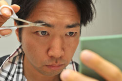 Primping: A man uses special scissors to trim his eyebrows. | YOSHIAKI MIURA PHOTO