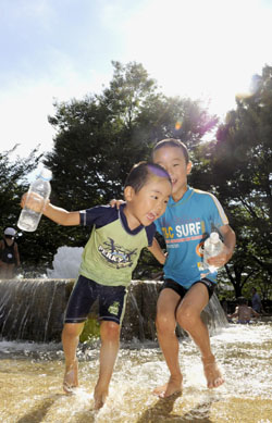 Hydrate: Boys beat the heat in a Tokyo park on Aug. 7. | KYODO PHOTO