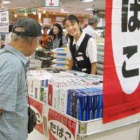 Time to quit: A man checks out cigarette cartons at a Daiei supermarket in Tokyo on Sept. 11 ahead of a record-high tobacco tax hike. | KYODO PHOTO