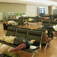 Making do: Passengers try to sleep on chairs in Haneda airport's international terminal. | TAKAHIRO FUKADA PHOTO