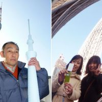 Tall order: Koji Imagawa, who sells Tokyo Sky Tree souvenirs, holds a plastic coin bank modeled on the tower outside his store near the new landmark in Sumida Ward, Tokyo, on Dec. 26. Right: Women pose the same day in front of a mirror at the foot of Sky Tree that enables visitors to take photos of themselves with the soaring tower in the background. | KYODO PHOTO