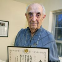 Twist of fate: Holocaust survivor Samuil Manski holds a certificate of the Japanese government's gratitude for years of spreading the story of Chiune Sugihara, a wartime Japanese diplomat in Lithuania who granted lifesaving visas to Jews, at his home in Massachusetts. | KYODO PHOTO