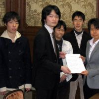 Mend the flaws: Kanagawa University student Atsushi Honma (center) and his group hand in their list of requests to fix the company recruiting system to Democratic Party of Japan lawmaker Saori Yoshikawa at the Diet on Jan. 18. | JUN HONGO PHOTO