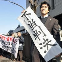 It's not over: A lawyer holds a sign that reads 'unjust decision' Friday after the Tokyo High Court ruled the metropolitan government was not in the wrong for ordering his clients — teachers and other high school staff — from observing the national anthem and flag in school ceremonies. | KYODO PHOTO
