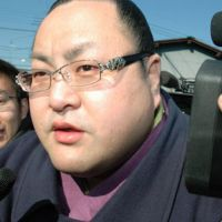 Busted: Enatsukasa, one of three sumo wrestlers who have reportedly admitted to participating in match-fixing, is surrounded by reporters Thursday as he leaves his stable in the city of Saitama. | KYODO PHOTO