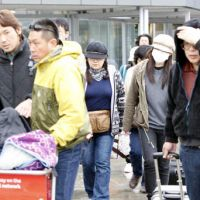 Praying for a miracle: Relatives of people linked to Toyama College of Foreign Languages who have been missing since Christchurch's massive earthquake arrive at the New Zealand city's airport Friday. | KYODO PHOTO