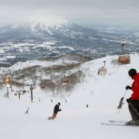 Economic lift: Mount Yotei is seen in the background as skiers and snowboarders go down a slope in Niseko, Hokkaido, on Feb. 6. | AP PHOTO