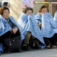 Elderly women huddle in blankets after being evacuated in Tokyo. | KYODO PHOTO