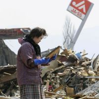 Shattered lives: A woman recovers a photo frame Sunday from the debris of her house in the city of Ofunato, Iwate Prefecture. | KYODO PHOTO