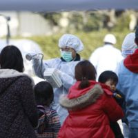 Radiation check: Residents evacuated from areas surrounding Fukushima's nuclear facilities are checked for radiation exposure Sunday. | AP PHOTO