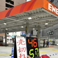 Supply disruptions: An employee at an Eneos gas station in Shibuya Ward, Tokyo, posts a sign Monday saying the station is sold out. | YOSHIAKI MIURA PHOTO